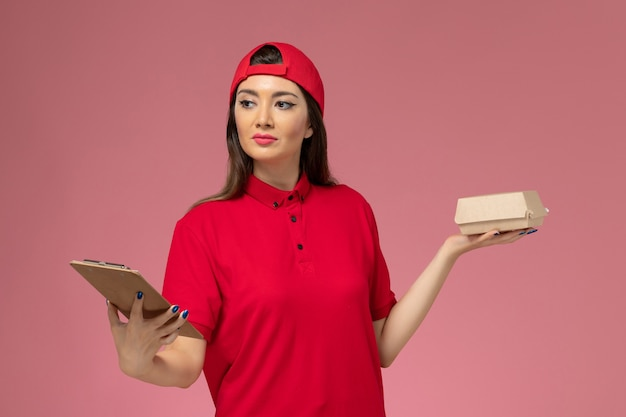 Front view young female courier in red uniform cape with little delivery food package and notepad on her hands on pink wall