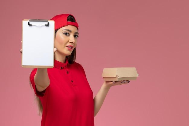Giovane corriere femminile di vista frontale in mantello rosso uniforme con poco pacchetto di cibo di consegna e blocco note sulle sue mani sulla parete rosa