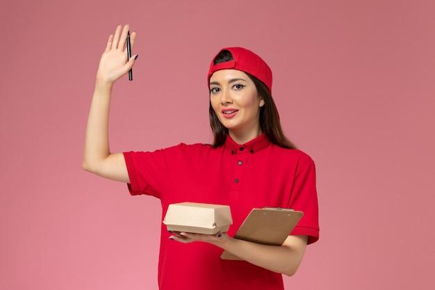 Corriere femmina giovane vista frontale in mantello rosso uniforme con piccolo pacchetto di cibo per la consegna e blocco note con la penna sulle mani sul muro rosa chiaro