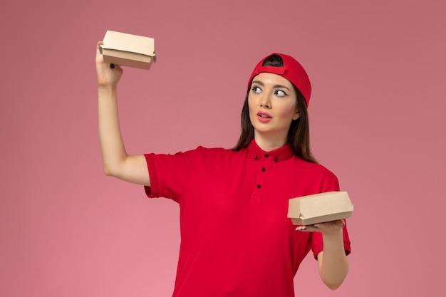 Corriere femminile giovane vista frontale in uniforme rossa e mantello con piccoli pacchi di cibo di consegna sulle sue mani sulla consegna del servizio uniforme scrivania rosa