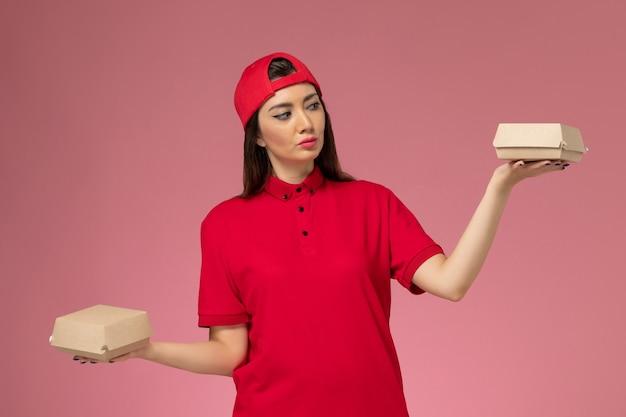 Corriere femmina giovane vista frontale in uniforme rossa e mantello con piccoli pacchi di cibo di consegna sulle sue mani sul muro rosa
