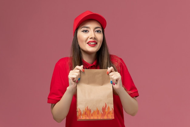 Front view young female courier in red uniform holding paper food package on pink background worker service delivery uniform company job