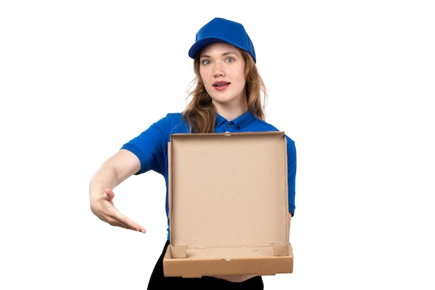 A front view young female courier in uniform holding an empty pizza box