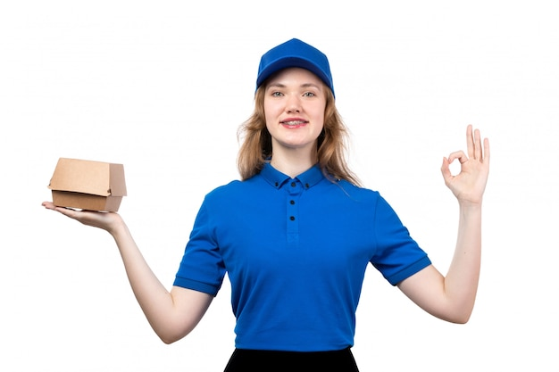 A front view young female courier in uniform holding food delivery package smiling