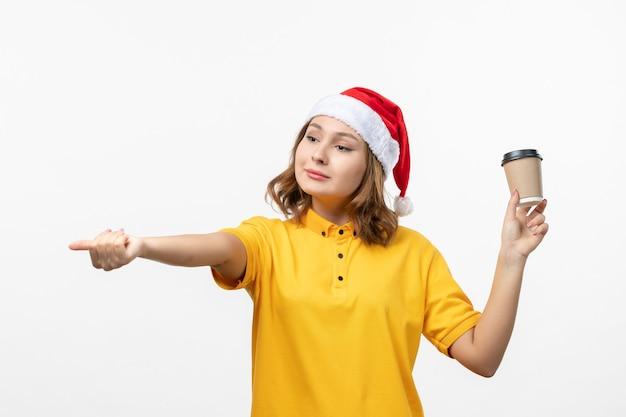 正面図白い壁の上のコーヒーと若い女性の宅配便制服サービス提供