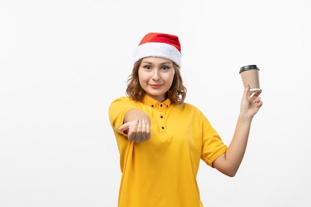 Вид спереди молодая женщина-курьер с кофе на белой стене единообразной доставки услуг