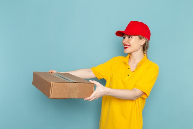 Front view young female courier in yellow shirt and red cape giving  package smiling on the blue space  job