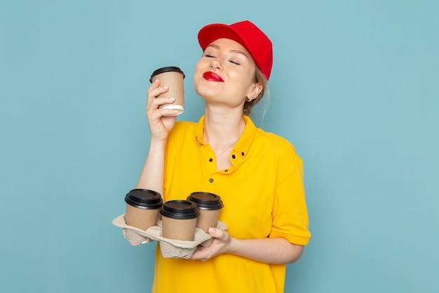 Giovane corriere femminile di vista frontale in camicia gialla e mantello rosso che tiene le tazze di caffè sul lavoro di spazio blu