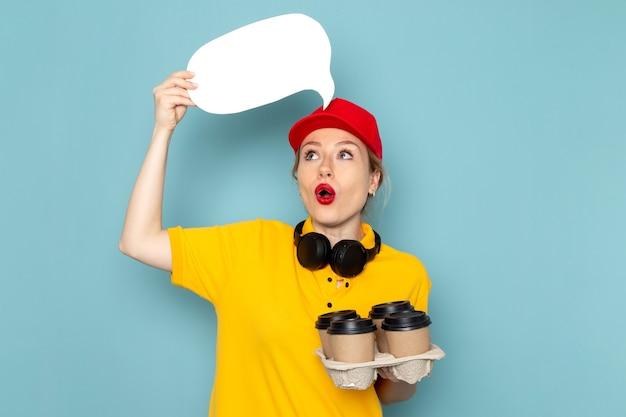 Giovane corriere femminile di vista frontale in camicia gialla e mantello rosso che tiene il segno bianco delle tazze di caffè sul lavoro dello spazio blu
