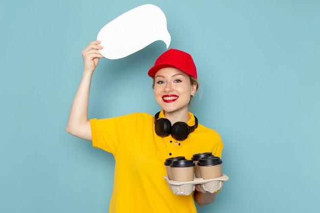 Giovane corriere femminile di vista frontale in camicia gialla e mantello rosso che tiene le tazze di caffè segno bianco sullo spazio blu