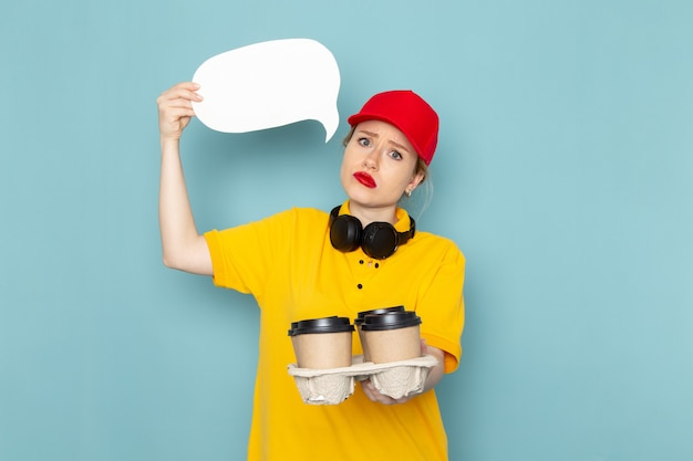 Front view young female courier in yellow shirt and red cape holding coffee cups white sign on the blue space