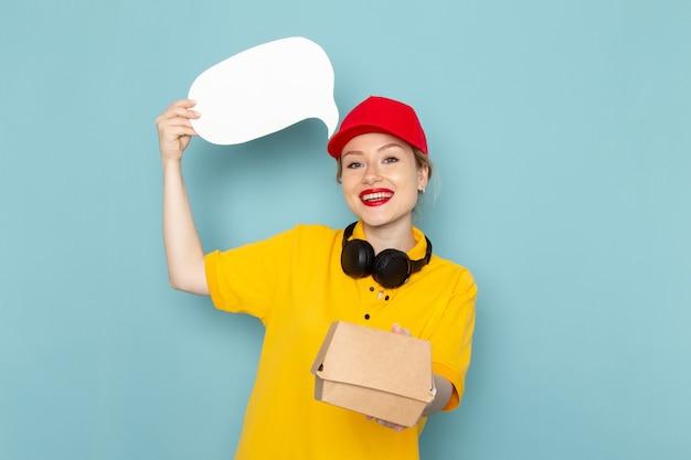 Giovane corriere femminile di vista frontale in camicia gialla e mantello rosso che tiene il pacchetto alimentare e segno bianco sullo spazio blu