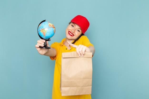 Giovane corriere femminile di vista frontale in camicia gialla e pacchetto rosso del globo della tenuta del mantello che parla sul telefono sull'uniforme di lavoro dello spazio blu