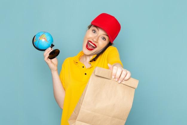 Giovane corriere femminile di vista frontale in camicia gialla e pacchetto rosso del globo della tenuta del mantello che parla sul telefono sullo spazio blu