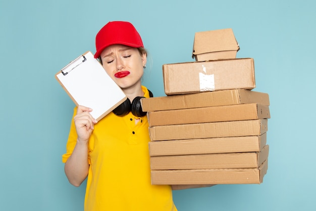 Front view young female courier in yellow shirt and red cape holding multiply  packages and notepad on the blue space   work