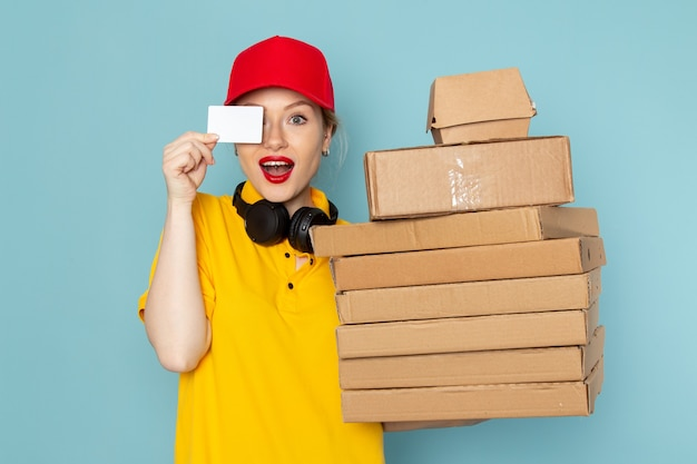 Front view young female courier in yellow shirt and red cape holding multiply  packages with card on the blue space   job