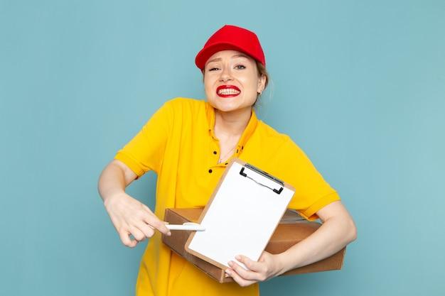 Giovane corriere femminile di vista frontale in camicia gialla e blocco note rosso del pacchetto della tenuta del mantello sul lavoro del pavimento blu
