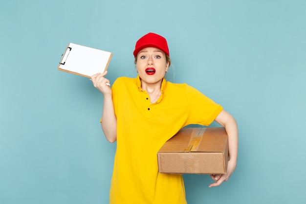 Giovane corriere femminile di vista frontale in camicia gialla e pacchetto rosso della tenuta del mantello e blocco note sul lavoratore di lavoro dello spazio blu