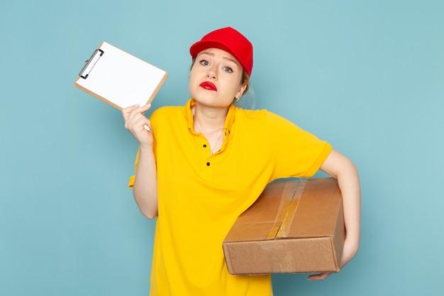 Giovane corriere femminile di vista frontale in camicia gialla e blocco note rosso del pacchetto della tenuta del mantello sul lavoro dello spazio blu