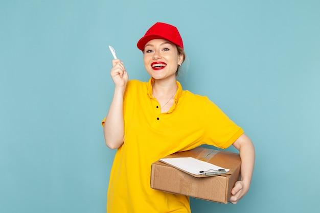 Giovane corriere femminile di vista frontale in camicia gialla e blocco note rosso del pacchetto della tenuta del mantello che sorride sul lavoro di lavoro dello spazio blu