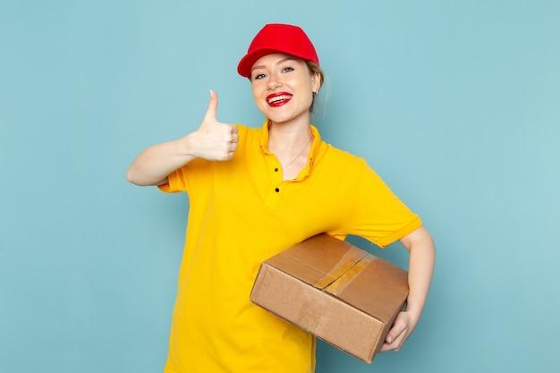 Giovane corriere femminile di vista frontale in camicia gialla e pacchetto rosso della tenuta del mantello che sorride sul lavoro dello spazio blu