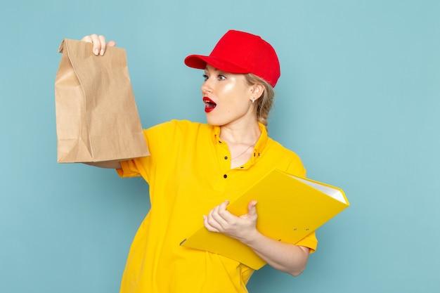 Giovane corriere femminile di vista frontale in camicia gialla e pacchetto rosso della tenuta del mantello e file giallo sul lavoro di spazio blu