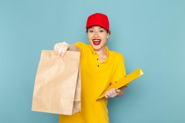Giovane corriere femminile di vista frontale in camicia gialla e pacchetto rosso della tenuta del mantello e file giallo sullo spazio blu