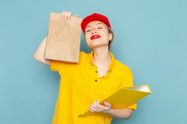 Giovane corriere femminile di vista frontale in camicia gialla e pacchetto rosso della tenuta del capo e archivio giallo che sorride sull'operaio blu dello spazio