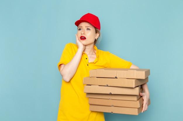 Giovane corriere femminile di vista frontale in camicia gialla e mantello rosso che tiene i pacchetti sullo spazio blu