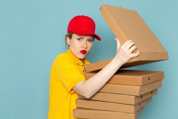Giovane corriere femminile di vista frontale in camicia gialla e mantello rosso che tiene i pacchetti che li aprono sullo spazio blu