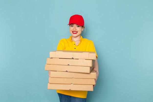 Giovane corriere femminile di vista frontale in camicia gialla e mantello rosso che tiene i pacchetti che sorridono sul lavoro dello spazio blu