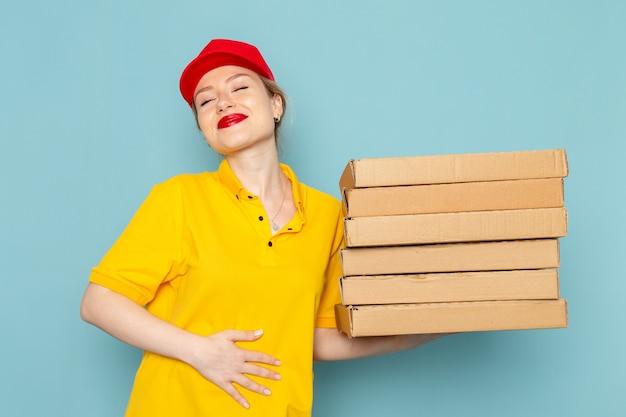 Giovane corriere femminile di vista frontale in camicia gialla e mantello rosso che tiene i pacchetti che sorridono sull'operaio blu dello spazio