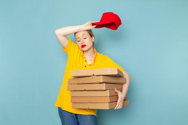 Giovane corriere femminile di vista frontale in camicia gialla e mantello rosso che tiene i pacchetti che decollano sul lavoro dello spazio blu