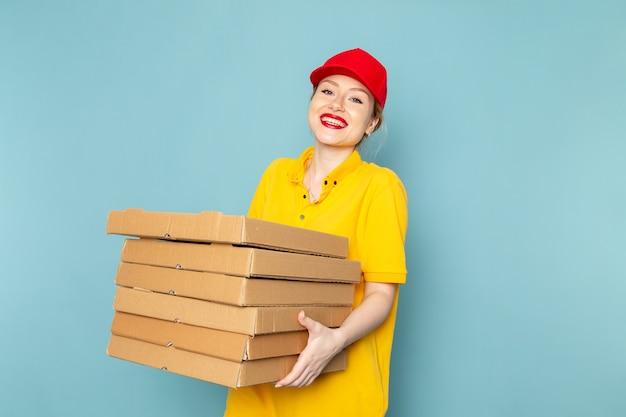 Giovane corriere femminile di vista frontale in camicia gialla e mantello rosso che tiene i pacchetti con il sorriso sul lavoro dello spazio blu