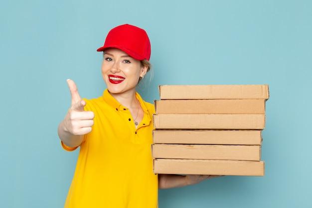 Giovane corriere femminile di vista frontale in camicia gialla e mantello rosso che tiene i pacchetti con il sorriso sull'operatore spaziale blu