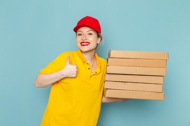 Giovane corriere femminile di vista frontale in camicia gialla e mantello rosso che tiene i pacchetti con il sorriso sullo spazio blu