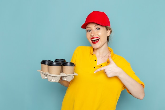 Front view young female courier in yellow shirt and red cape holding plastic coffee cups on the blue space   job