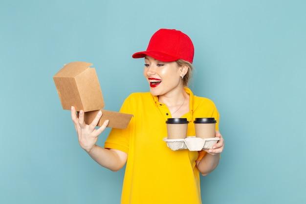 Giovane corriere femminile di vista frontale in camicia gialla e mantello rosso che tiene le tazze di caffè di plastica e il pacchetto dell'alimento che sorridono sullo spazio blu