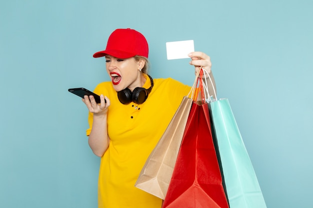 Front view young female courier in yellow shirt and red cape holding shopping packages talking on the phone on the blue space   job