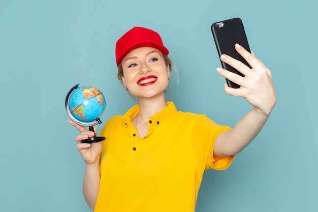 Front view young female courier in yellow shirt and red cape taking a selfie with globe on the blue space