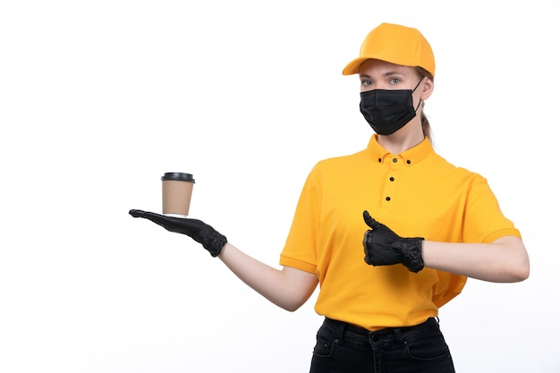 A front view young female courier in yellow uniform black gloves and black mask holding coffee cup showing like sign
