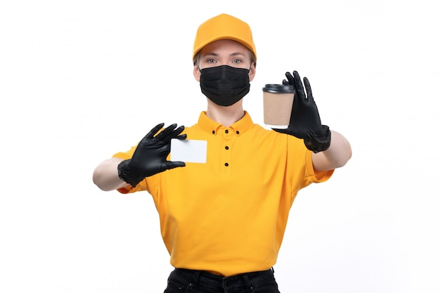 A front view young female courier in yellow uniform black gloves and black mask holding coffee cup and white card