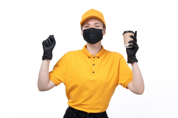 A front view young female courier in yellow uniform black gloves and black mask holding coffee cup with great mood