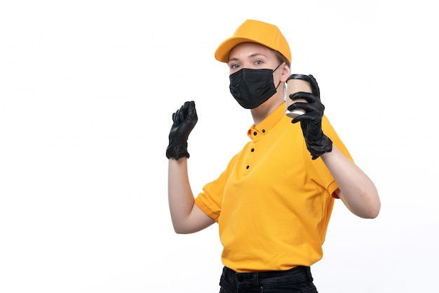 A front view young female courier in yellow uniform black gloves and black mask holding coffee cup