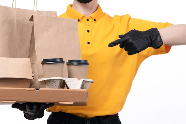 A front view young female courier in yellow uniform black gloves and black mask holding coffee cups and food delivery packages