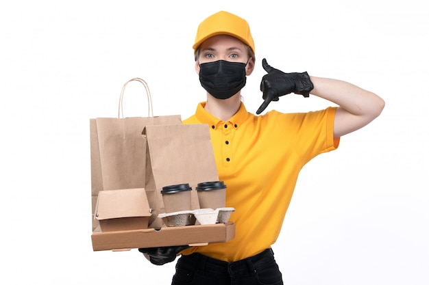 A front view young female courier in yellow uniform black gloves and black mask holding coffee cups and food packages delivering