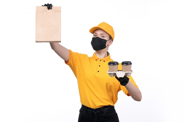 A front view young female courier in yellow uniform black gloves and black mask holding coffee cups and package