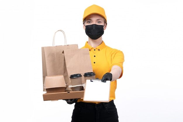 A front view young female courier in yellow uniform black gloves and black mask holding coffee cups and packages asking for the signature on the white desk service delivering job