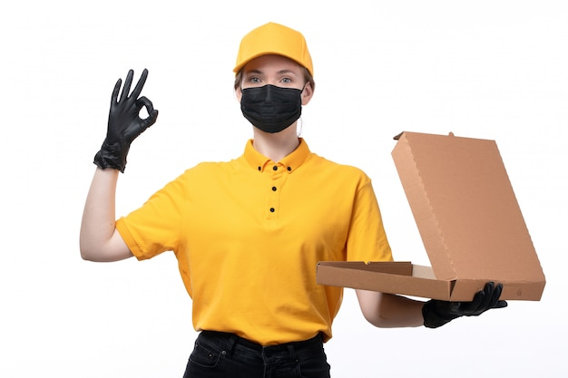 A front view young female courier in yellow uniform black gloves and black mask holding an empty pizza box