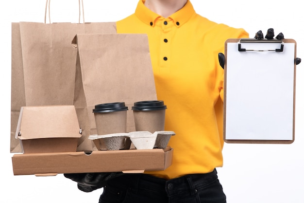 A front view young female courier in yellow uniform black gloves and black mask holding food packages and coffee cups